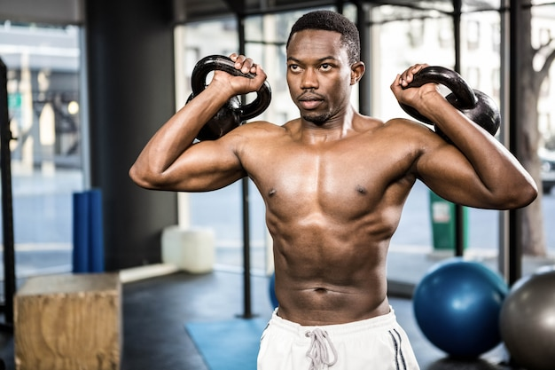 Homem sem camisa, levantando pesados kettlebells no ginásio crossfit