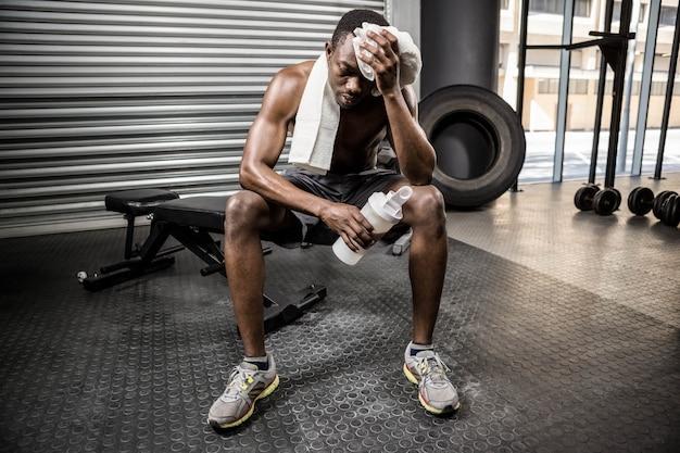 Homem sem camisa, limpando o suor com toalha no ginásio crossfit