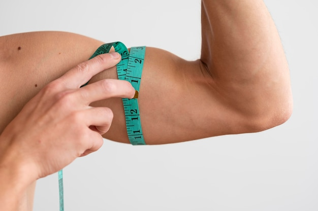 Homem sem camisa medindo seu bíceps com fita adesiva