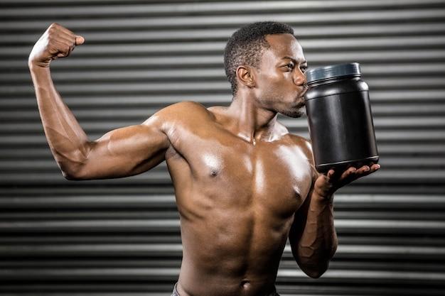 Homem sem camisa, mostrando o bíceps e beijar pode no ginásio crossfit