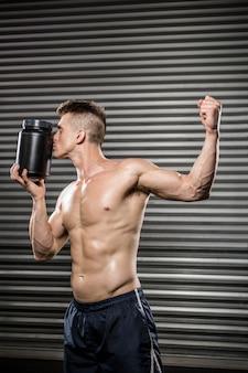 Homem sem camisa, mostrando o bíceps e beijar pode no ginásio