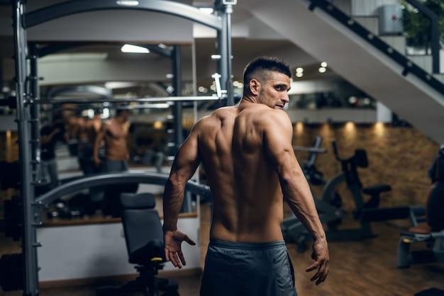 Homem sem camisa muscular caucasiano posando no ginásio. costas viradas.