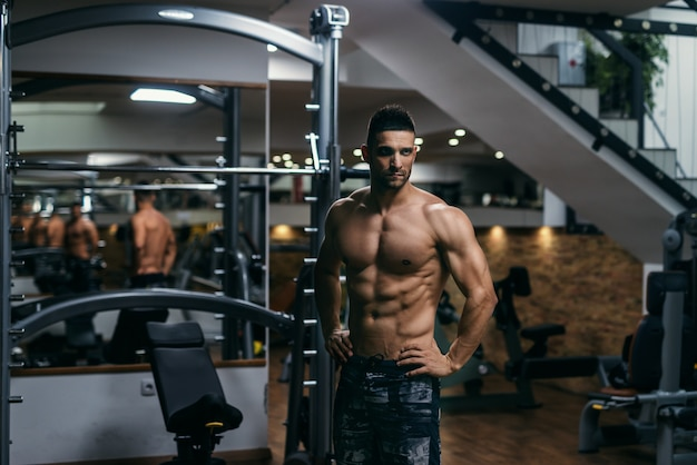 Homem sem camisa muscular com as mãos nos quadris, posando em uma academia