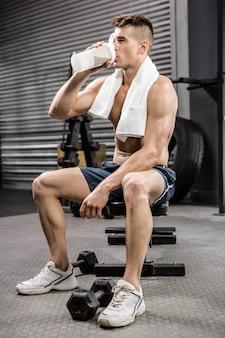Homem sem camisa no banco bebendo shake de proteína no ginásio
