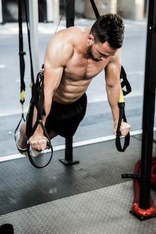 Homem sem camisa pendurado na corda no ginásio crossfit
