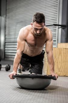 Homem sem camisa planking na bola bosu no ginásio crossfit