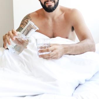Homem sem camisa, sentado na cama com um copo de água
