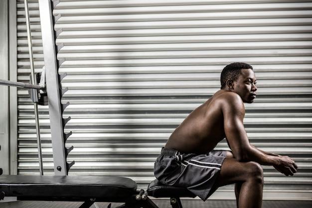Homem sem camisa, sentado no banco no ginásio crossfit