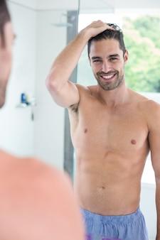 Homem sem camisa, sorrindo enquanto olha no espelho