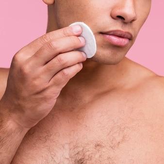 Homem sem camisa usando almofadas de algodão no rosto
