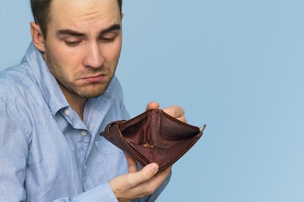 Homem sem dinheiro. empresário segurando uma carteira vazia. homem mostrando carteira vazia ao mostrar a inconsistência e a falta de dinheiro e a incapacidade de pagar o empréstimo e a hipoteca.