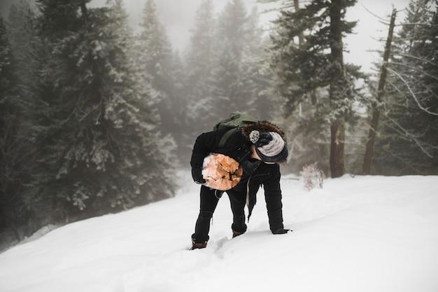 Homem sem rosto, carregando lenha