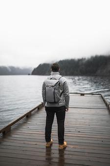 Homem sem rosto em pé no cais