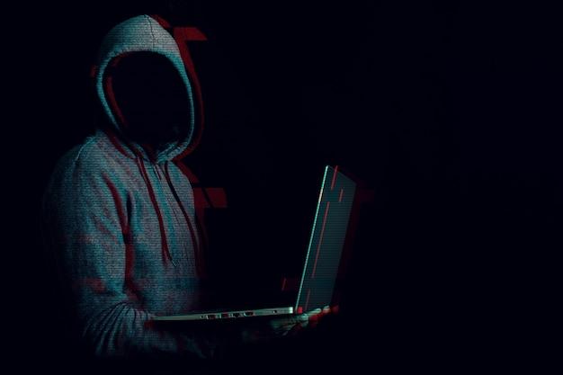 Homem sem rosto em um capuz segura um laptop nas mãos em um escuro