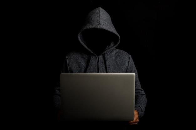 Homem sem rosto em um capuz segurando um laptop no escuro
