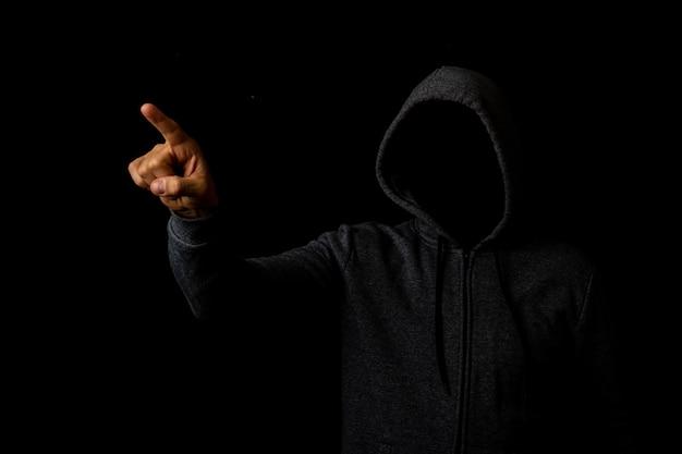 Homem sem rosto em um capuz toca o dedo em um fundo escuro.