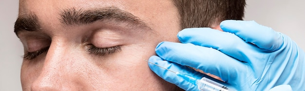 Homem sendo injetado em close-up do rosto