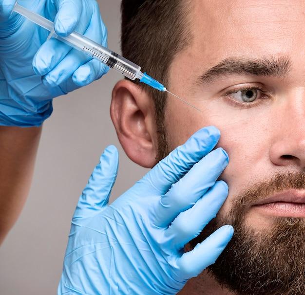 Homem sendo injetado no rosto