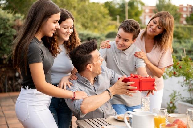 Homem sendo surpreendido com presente em reunião familiar