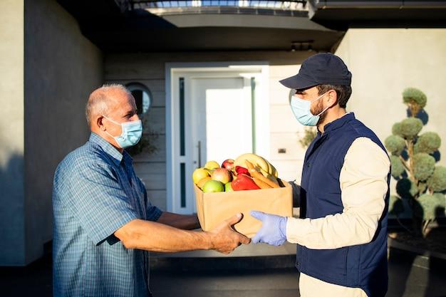Homem sênior aceitando entrega de comida do entregador durante a pandemia de covid19 ou bloqueio.