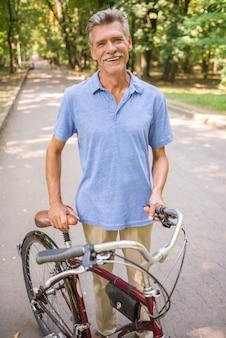 Homem sênior alegre com a bicicleta no parque.
