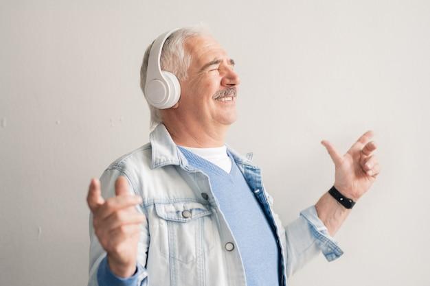 Homem sênior alegre com fones de ouvido, ouvindo sua música favorita e se divertindo sozinho