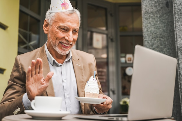 Homem sênior alegre comemorando aniversário com videochamada no terraço do café