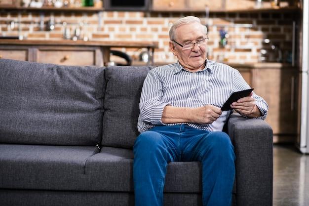 Homem sênior alegre sentado no sofá enquanto lê um livro eletrônico