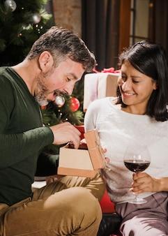 Homem sênior animado, abrindo seu presente