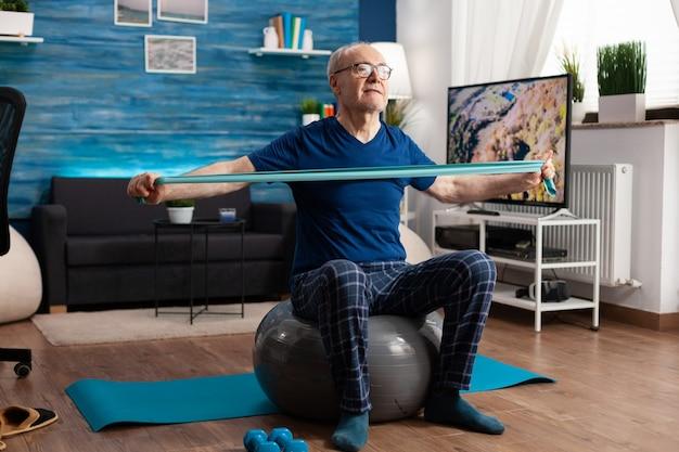 Homem sênior aposentado alegre exercitando os músculos do braço usando uma faixa elástica de resistência praticando exercícios aeróbicos