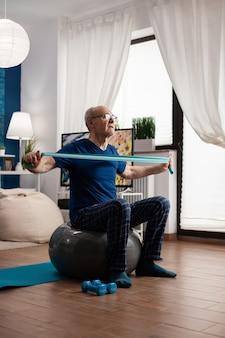 Homem sênior aposentado e alegre exercitando os músculos do braço usando um elástico