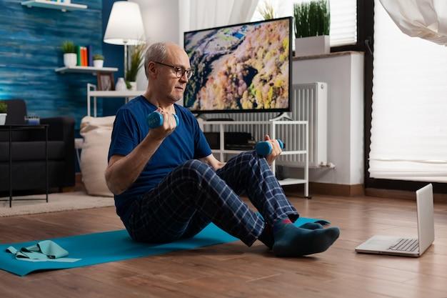 Homem sênior aposentado sentado em um tapete de ioga, alongando os músculos abdominais, praticando exercícios físicos
