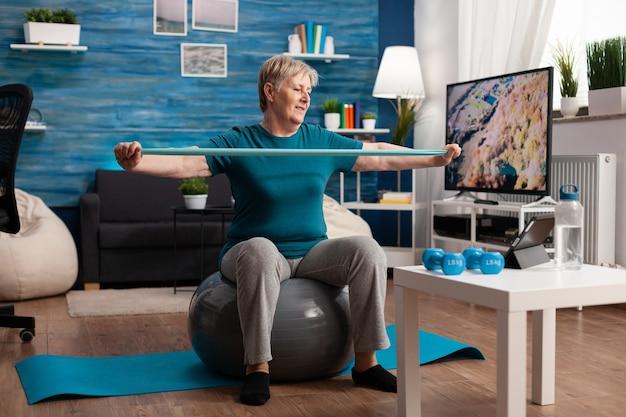 Homem sênior aposentado sentado na bola suíça de fitness na sala de estar, fazendo exercícios de fitness de bem-estar, alongando os músculos do braço usando elástico de aeróbica