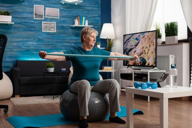 Homem sênior aposentado sentado na bola suíça de fitness na sala de estar fazendo exercícios de fitness e bem-estar