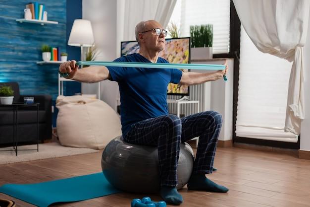 Homem sênior aposentado sentado na bola suíça na sala de estar, fazendo exercícios de fitness de saúde, alongando os músculos do braço usando faixa elástica de resistência. aposentado treinando força corporal na sala de estar