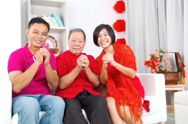 Homem sênior asiático e crianças comemorando o ano novo chinês