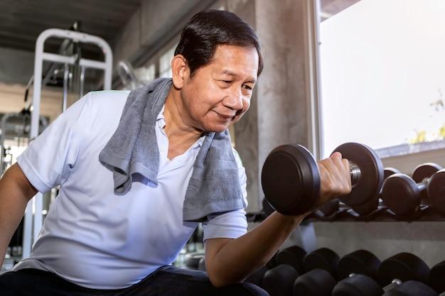 Homem sênior asiático no treinamento de sportswear com halteres no ginásio.