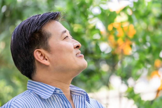 Homem sênior asiático que pensa e que relaxa no parque.