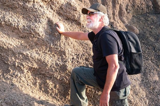 Homem sênior ativo com mochila, caminhadas montanha árida à luz do sol. pessoas de cabelos brancos e barba curtindo a liberdade