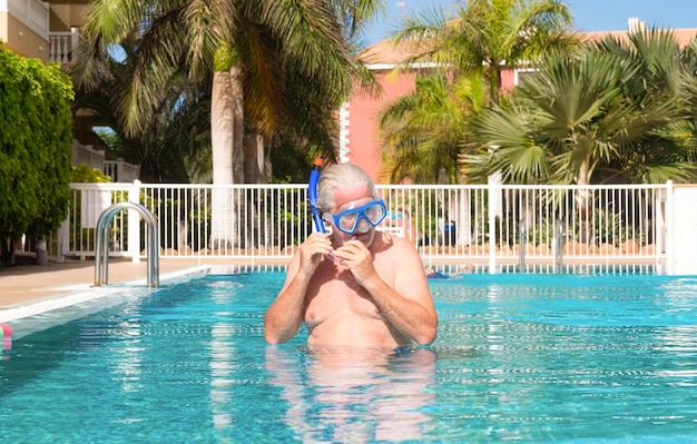 Homem sênior ativo fazendo exercícios na piscina, usando uma máscara de mergulho. aposentado feliz e estilo de vida saudável.