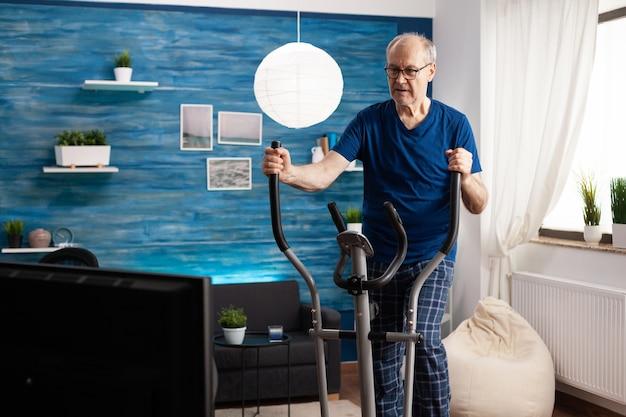 Homem sênior ativo, treinamento de pernas, resistência muscular, ciclismo, máquina de bicicleta na sala de estar, durante o treino de estilo de vida saudável. aposentado assistindo a um vídeo de fitness na televisão para seu bem-estar