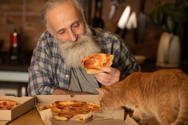Homem sênior barbudo com seu gato vermelho, comendo pizza em casa cozinha.