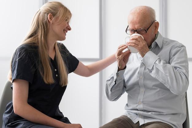 Homem sênior bebendo água com enfermeira consolando-o