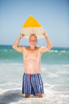 Homem sênior carregando prancha de surfe