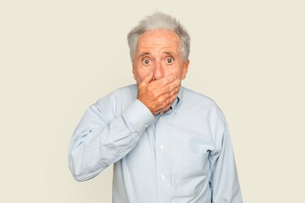 Homem sênior chocado com a mão cobrindo a boca