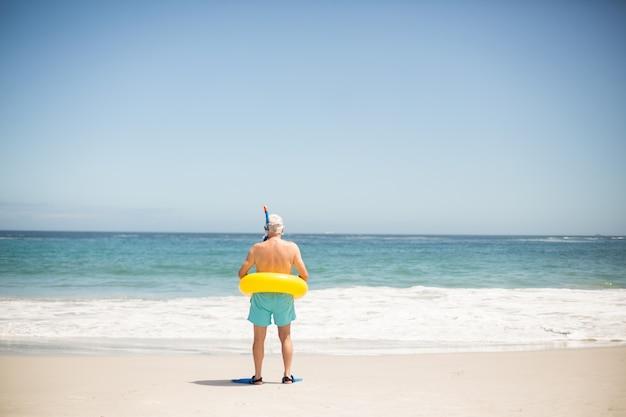Homem sênior com anel de natação e nadadeiras na praia