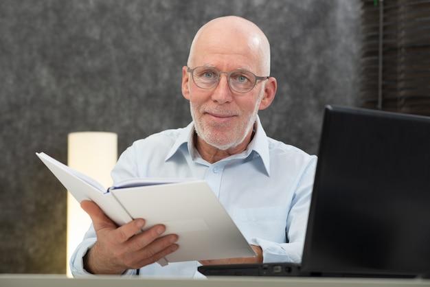 Homem sênior, com, branca, cabelos, e, óculos, livro leitura