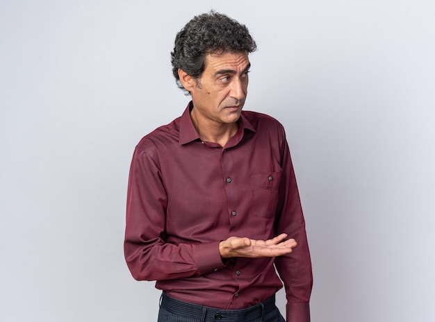 Homem sênior com camisa roxa parecendo confuso, levantando o braço em desprazer e indignação