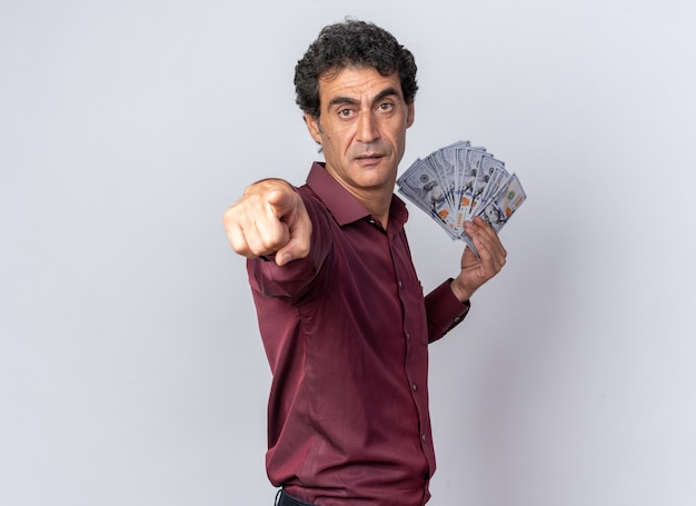 Homem sênior com camisa roxa segurando dinheiro e apontando com o dedo indicador para a câmera, parecendo surpreso em pé sobre um fundo branco