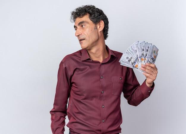 Homem sênior com camisa roxa segurando dinheiro e olhando de lado feliz e confiante em pé sobre o branco